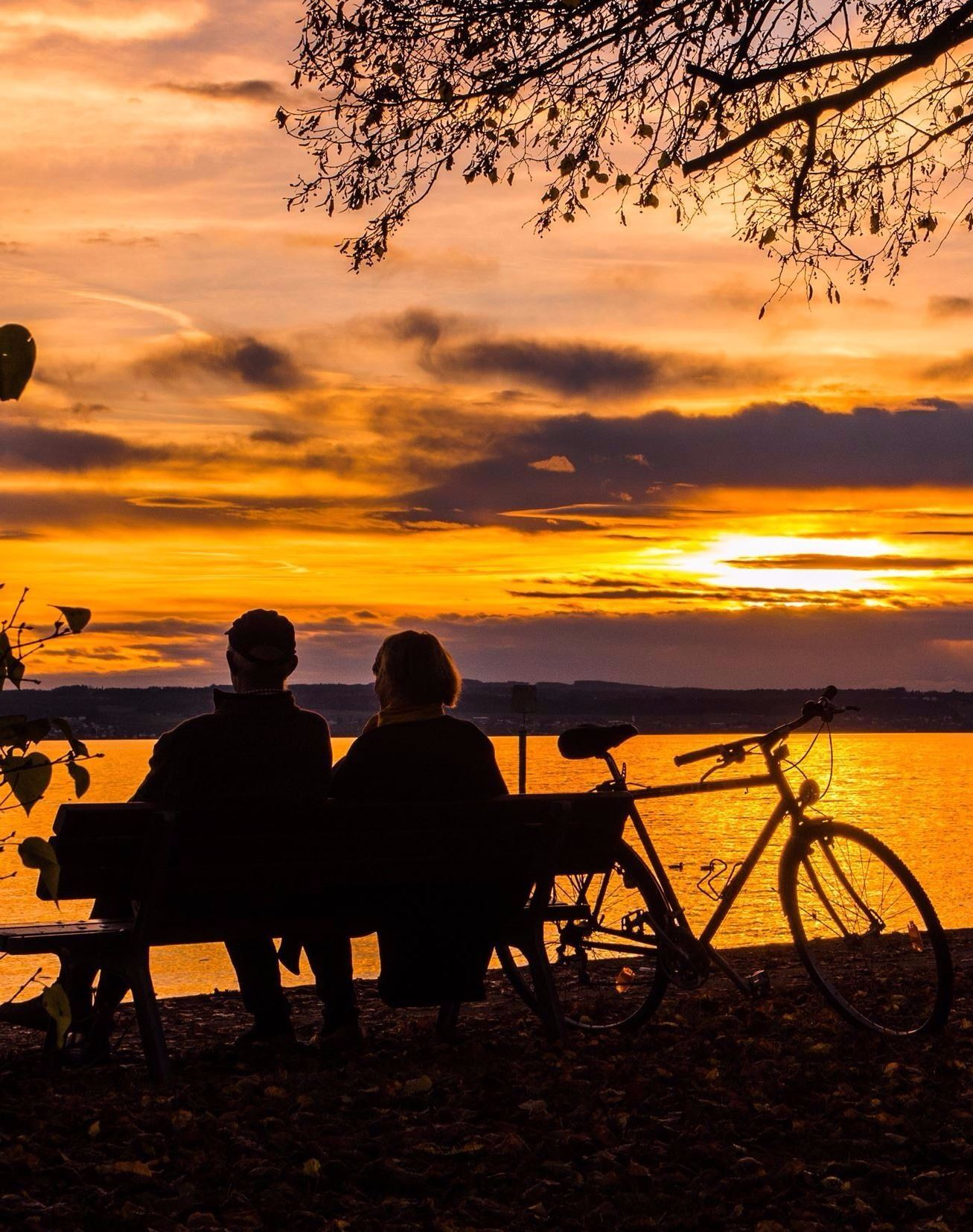 Image of a sunset silhouette of two people sitting on a park bench with a bike